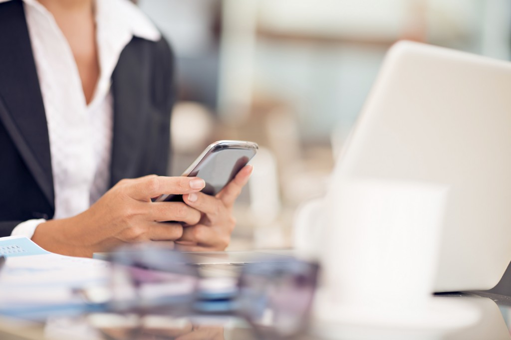 Cropped image of a businessperson dialing a number using the smartphone on the foreground